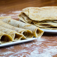 stack and rolls of homemade spelt tortiilas on white plate