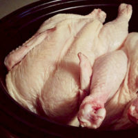two raw chickens in black crock pot