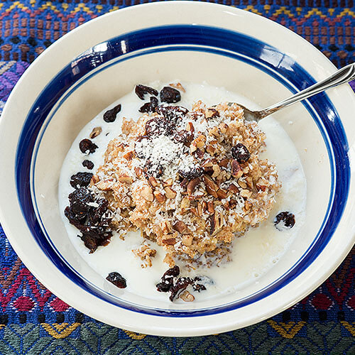 ceramic bowl with a blue stripe full of breakfast porridge, garnished with chopped nuts, raisins, and shredded coconut
