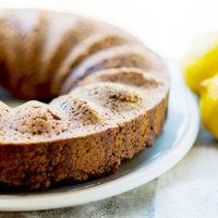 lemon spelt bundt cake on white plate with lemons in background