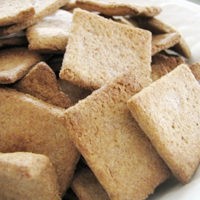 Stack of spelt crackers on white plate