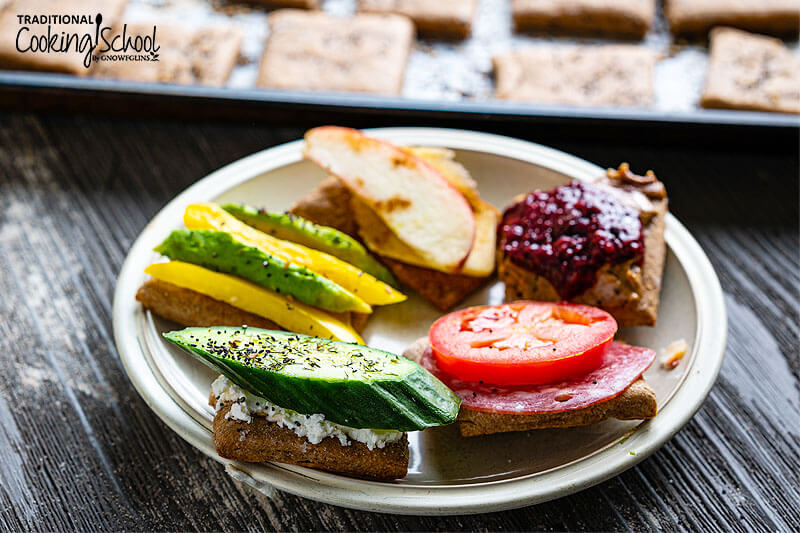 Homemade crackers topped with different spreads, fruits, and veggies.