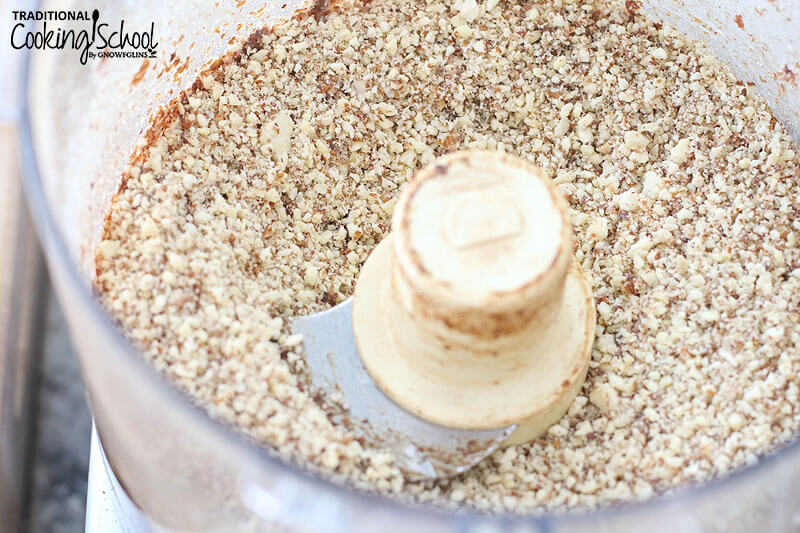 close-up shot of a food processor bowl with blade attached full of finely chopped nuts