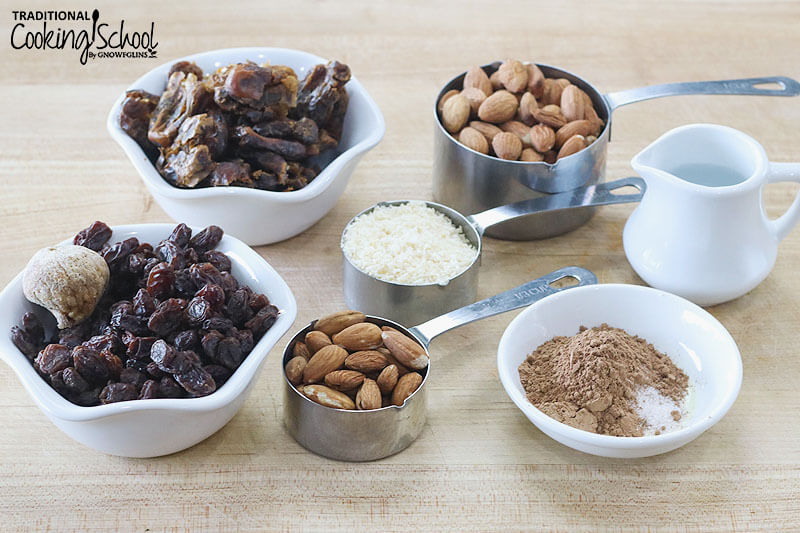 small white ceramic bowls and stainless steel measuring cups of various ingredients for homemade Larabars, including raisins and dates, almonds, shredded coconut, water, and cocoa powder on a butcher block cutting board