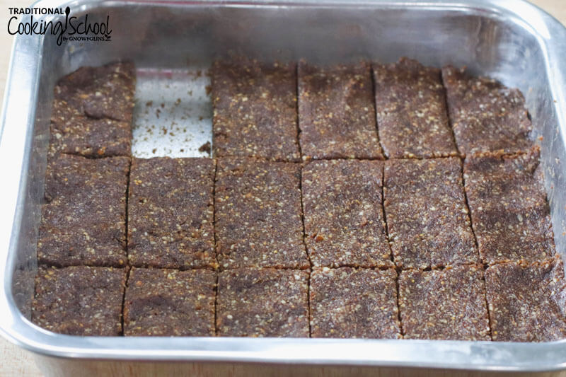 square stainless steel baking dish of homemade Larabar mixture cut into rectangles, with one Larabar missing