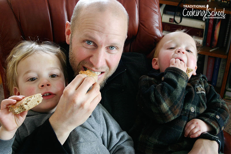 A dad with two kids sitting on his lap eating sourdough English muffins.