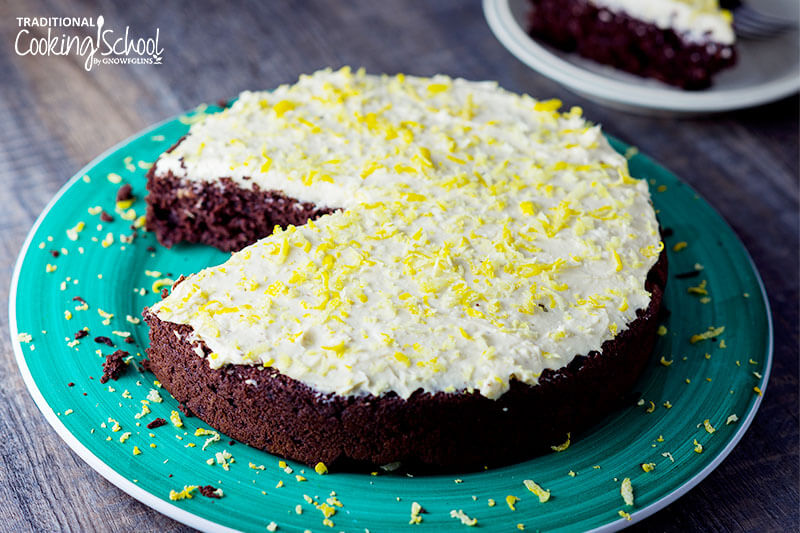 piece of chocolate torte with white frosting and lemon zest on blue plate
