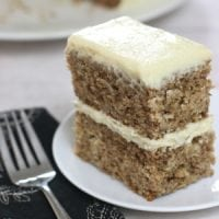 A double layered sourdough spice cake with cream cheese frosting between layers and on top sitting on a small white plate with a form beside it.