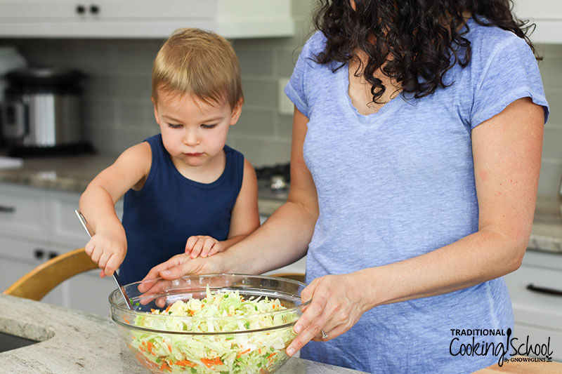 Woman and little boy stirring together vegetables in a large glass bowl for homemade kimchi.