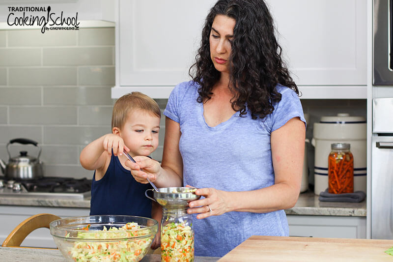 Woman and a little boy in a kitchen spooning kimchi mixture into a quart mason jar.