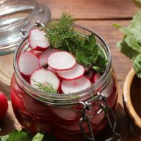 A weck jar filled with sliced lacto-fermented radishes and sprigs of fresh dill.