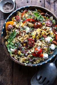 Large bowl filled with pasta salad that has mozarella, tomatoes, roasted corn and many other colorful veggies.