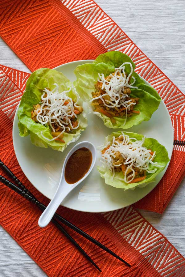 White plate with three lettuce cups filled with an asian chicken and a spoon filled with sauce sitting on a table over a red table runner.