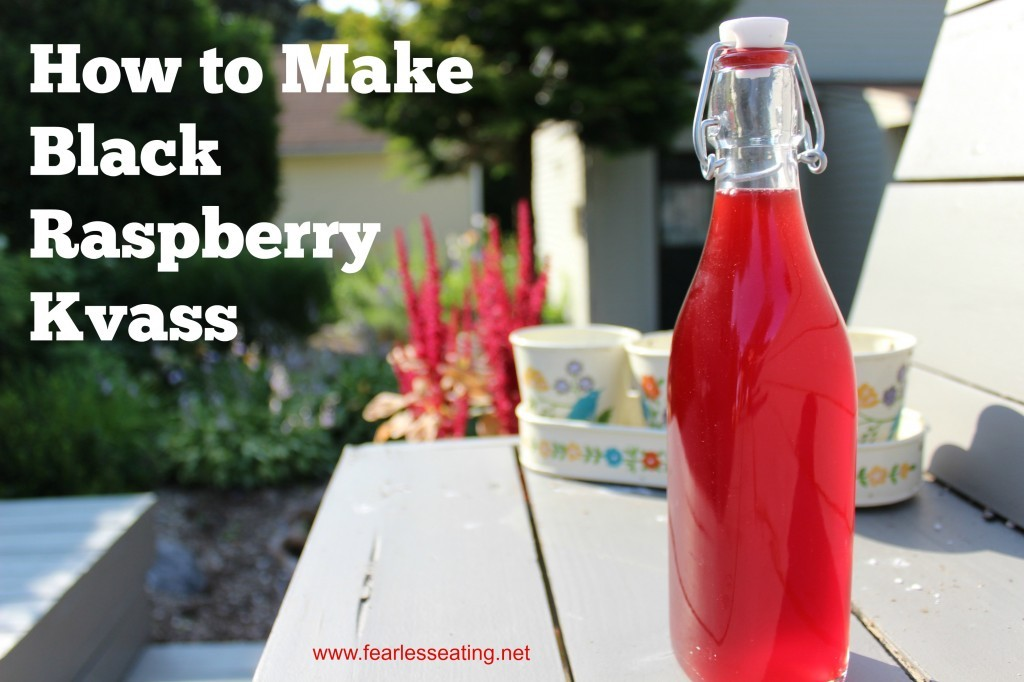 flip top bottle of bright red black raspberry kvass on an outside picnic table