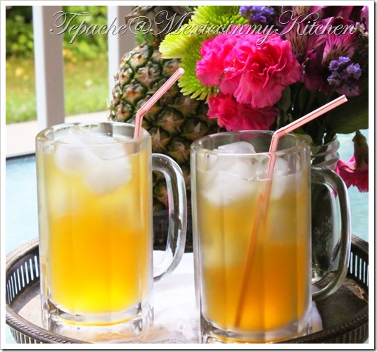 two glasses of bright yellow tepache with ice and straws