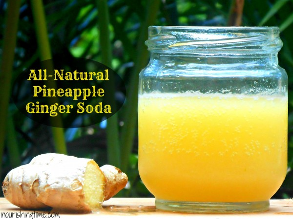 bubbly jar of pineapple ginger soda alongside half of a ginger root
