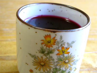 small cup with orange flowers on it containing deep purple beet kvass