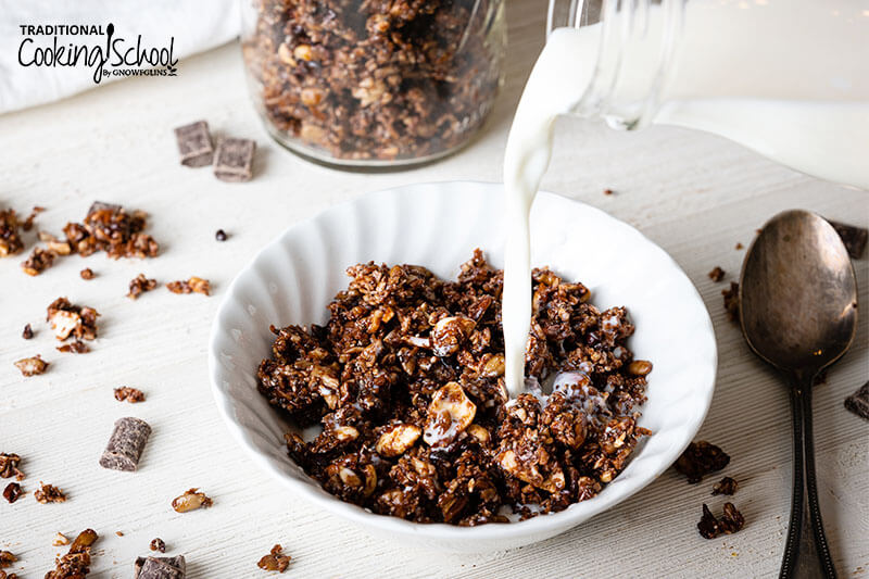 A white bowl filled with chocolate granola and milk being poured over the top.