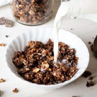 White bowl with chocolate paleo granola and milk being poured over the top