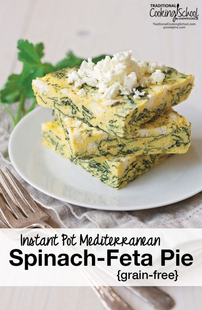 three squares of egg spinach pie stacked with feta cheese crumbled on top