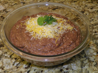bowl of refried beans with shredded cheese melting on top and a garnish of parlsey