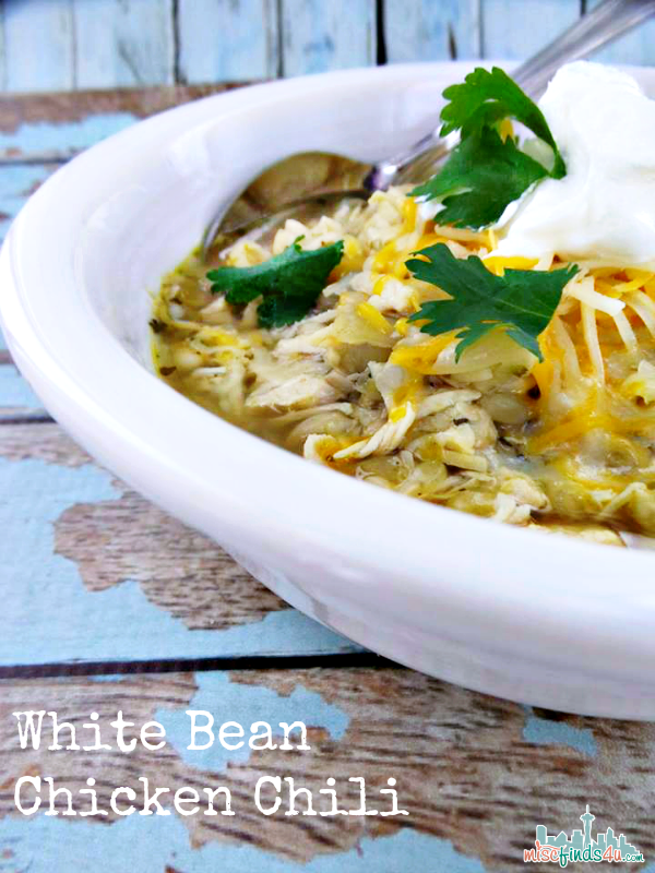 white bean and chicken chili with toppings of cheese, sour cream, and fresh parsley