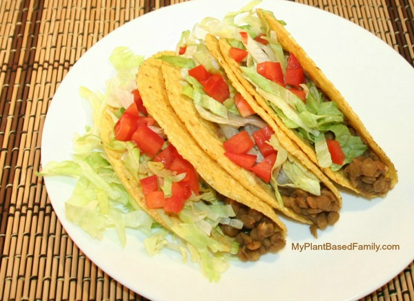 hard shell tacos with tomatoes, lentils, and lettuce spilling out