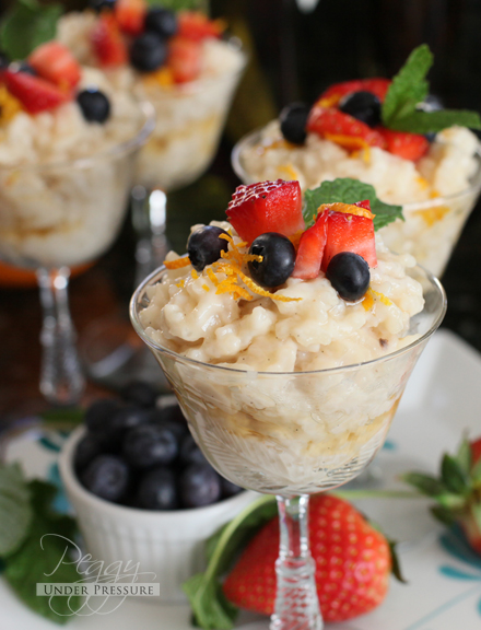 coconut rice pudding topped with orange zest, blueberries, strawberries, and a mint leaf