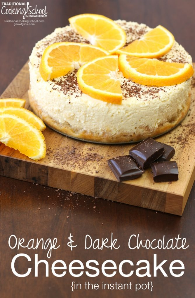 cheesecake topped with orange slices arranged in a spiral shape with chocolate shavings