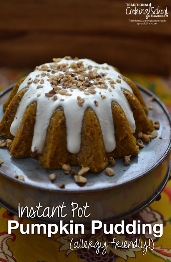 pumpkin pudding that has been cooked in a bundt pan with homemade whipped cream dripping down the side and chopped nuts sprinkled on top