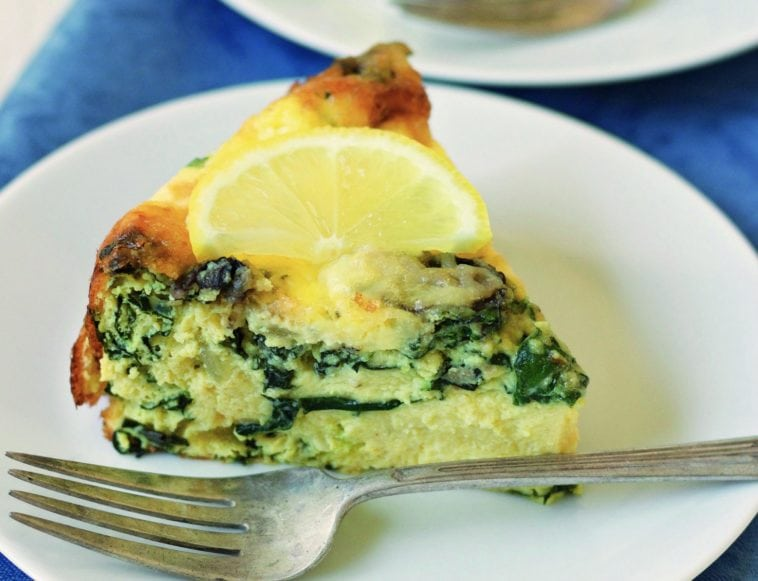 crustless quiche with a lemon slice on top on a plate with a fork