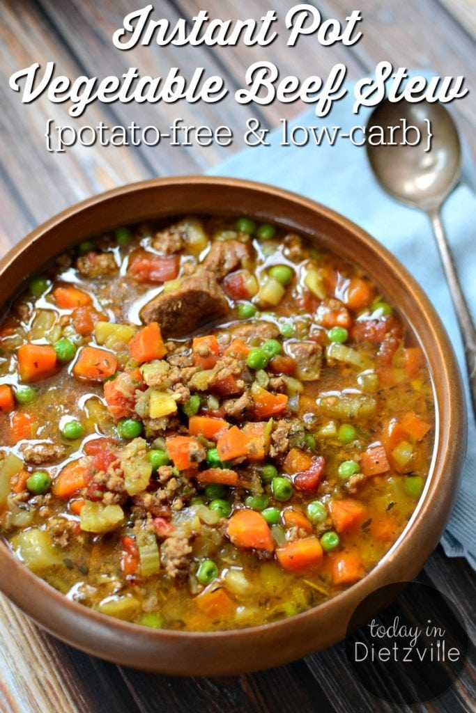 bowl of beef stew with lots of vegetables including carrots and peas