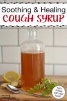 "Photo of a glass bottle filled with cough syrup, next to a spoon and fresh herbs including ginger root. Text overlay says: ""Soothing & Healing Cough Syrup (fight illness with real food!)"""