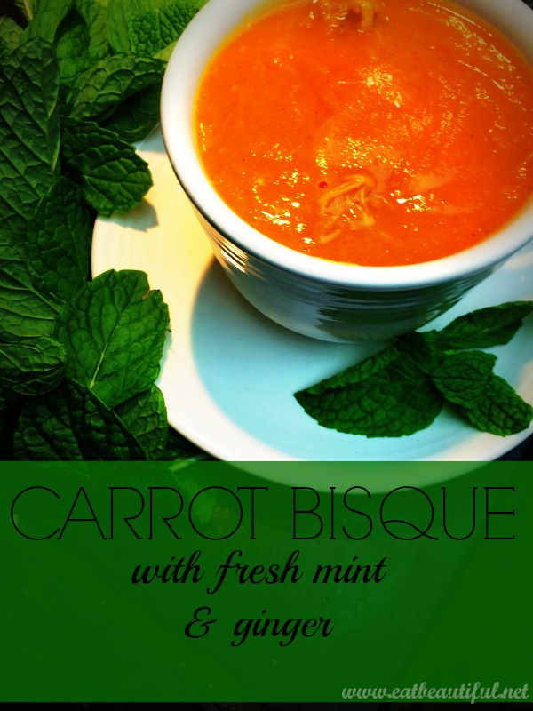 bowl of bright orange carrot bisque surrounded by mint leaves