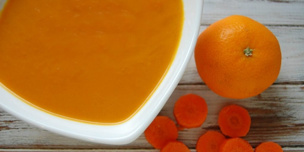 bright orange colored soup next to carrot rounds and a whole orange