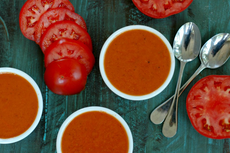 bowls of beautiful red tomato soup with sliced tomatoes nearby