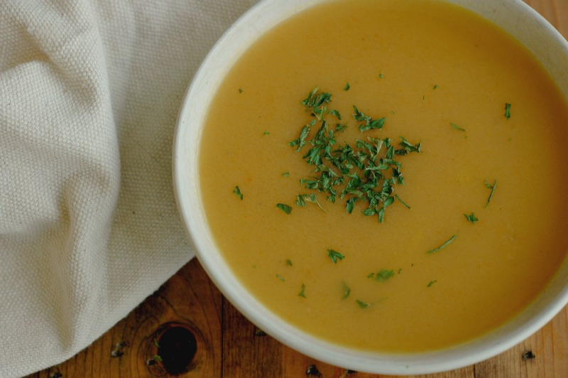 orange colored soup with herb garnish