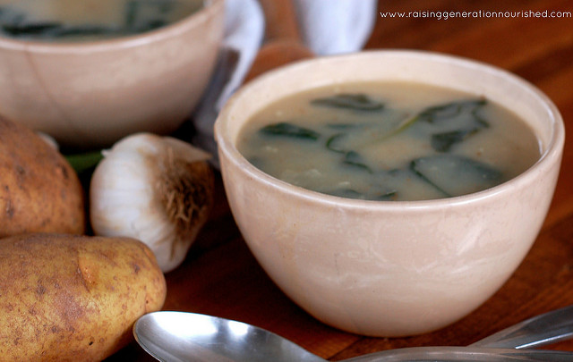 rustic bowl of creamy soup with spinach floating in it next to russet potatoes and a garlic bulb