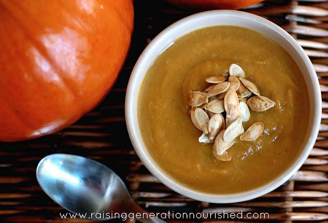 orange colored soup with pumpkin seeds for garnish