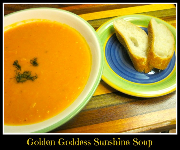 bright orange colored soup next to two pieces of sourdough bread