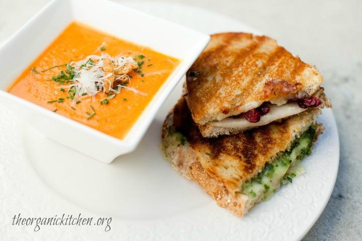 bright orange tomato soup next to grilled cheese sandwiches with pesto