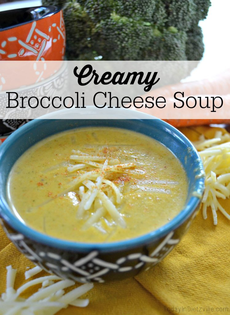 blue bowl of creamy soup with grated cheese and cayenne pepper for garnish