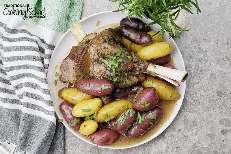 lamb roast with colored potatoes on white platter with rosemary and tea cloth