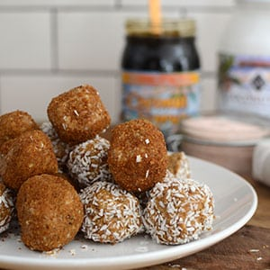 A white plate with salted caramel cookie dough bites piled high, some are coated in coconut flakes and others are dusted with coconut sugar.