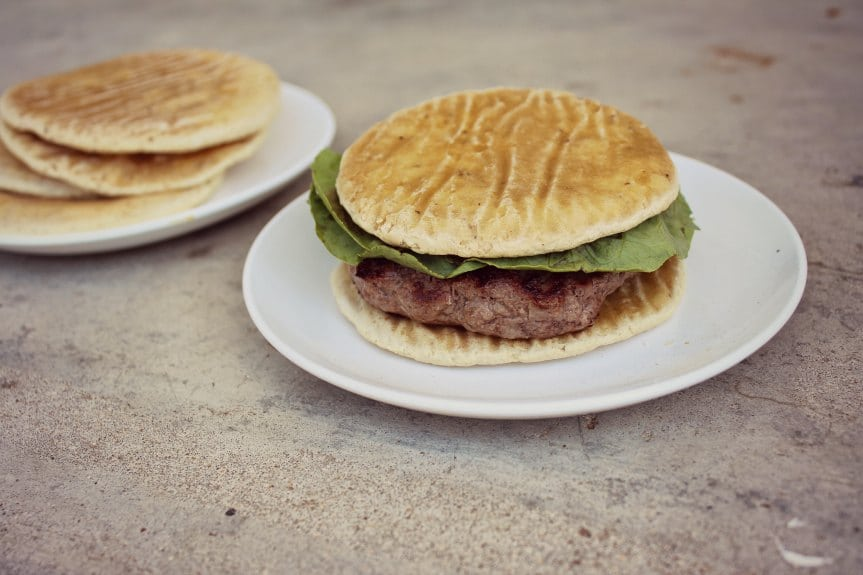 A hamburger with homemade bun on white plate on sidewalk