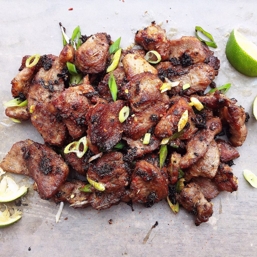 Vietnamese grilled lemongrass pork with limes on counter