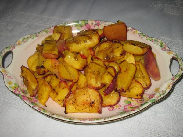 Grilled peaches on china plate and white linen table