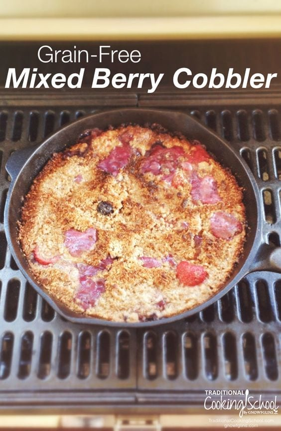 Berry cobbler in cast iron pan on grill with white text overlay