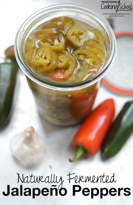 Jalapeno peppers in jar with whole jalapeno, onion with black text overlay