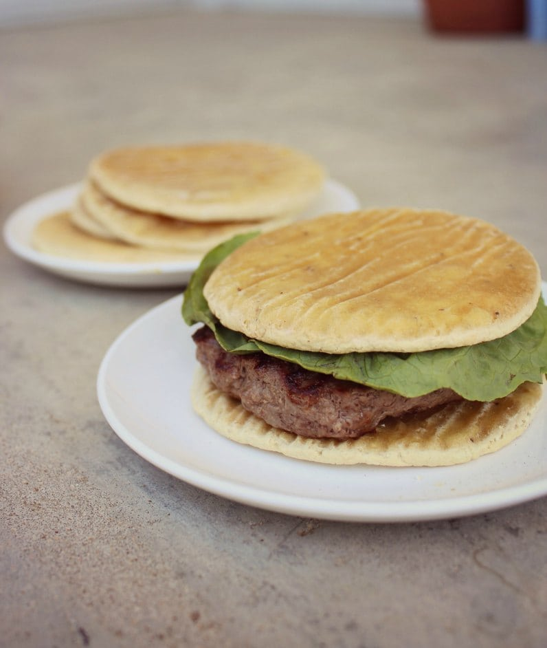 white plate with a hamburger that has thin buns
